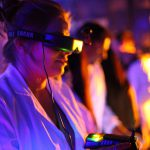 picture of a woman in a white lab coat with first person view goggles solving a futuristic puzzle