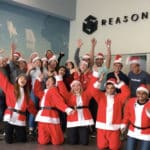 teams in santa costumes celebrating at reason