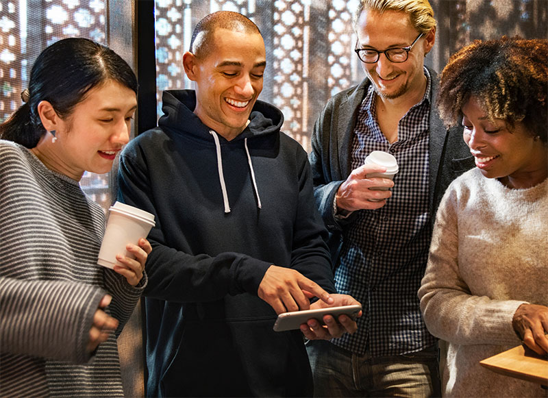 bunch of people smiling and looking at a tablet