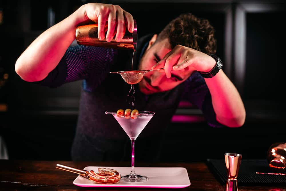 Professional bartender preparing martini with olives at bar counter. Dry vodka martini, cocktail served in restaurant, pub and bar. Long drink cocktail concept