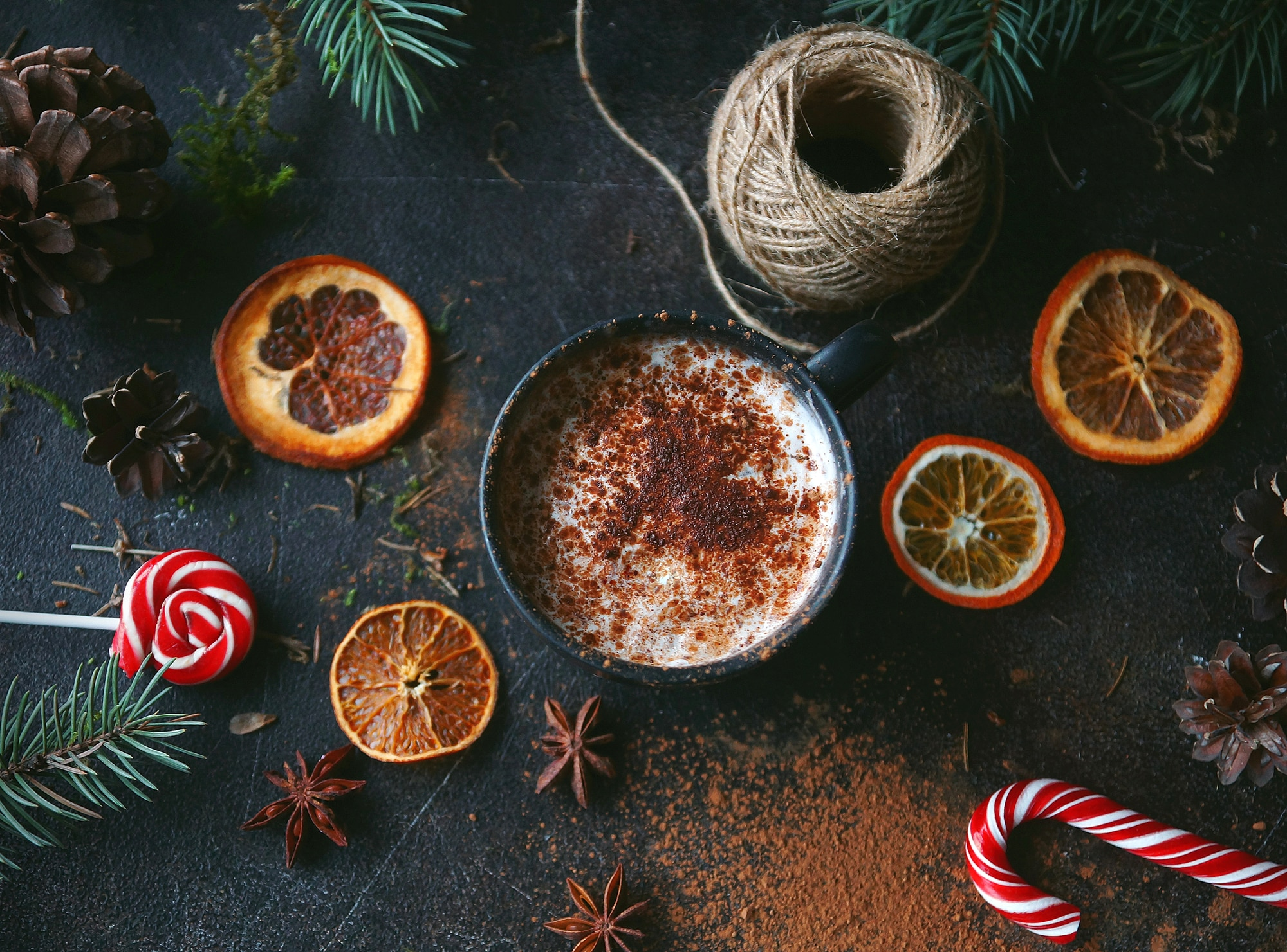 Christmas hot chocolate in a black cup with caramelized oranges, fir branches and candy cane on dark background, Selective focus